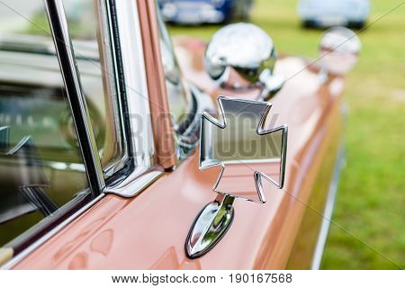 Fragment of a retro car with unusually (cross) rear view mirror.