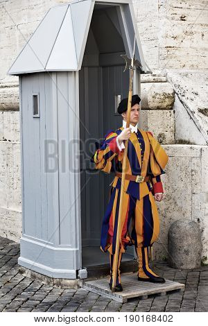 Rome,Vatican, Italy - April 14, 2017: Papal Swiss Guard in their traditional uniform stands guard at the entrance of Saint Peter's Basilica