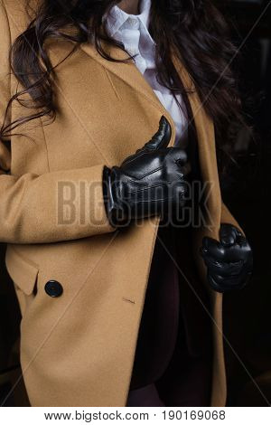 Female Hands In Black Leather Gloves On Lapels Wool Coat Camel