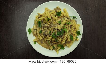 Italian Pasta with Mushrooms and Parsley on Whine Plate on Wooden Background