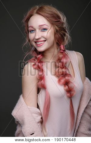The Girl With Pink Hair In Braids, And Pink-blue Makeup With A Pink Coat Worn Off The Shoulder Stand