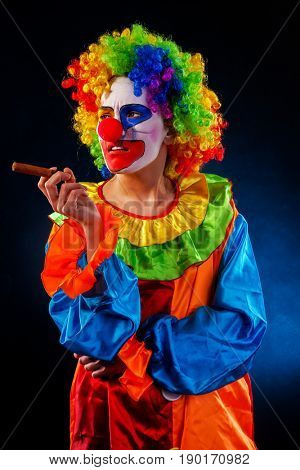Evil clown on black background. Mad woman is smoking cigar. Portrait of crazy female with an angry look after performance.