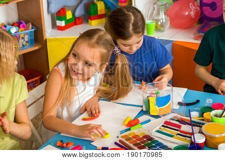 Child dough play in school. Plasticine for children. mold from plasticine in kindergarten .Kids knead modeling clay with hands in preschool. Zoo from plasticine.