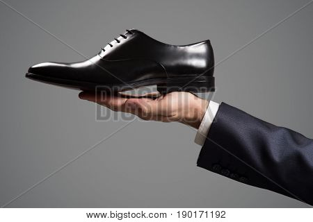 Businessman holding luxury leather shoes in hand. Close-up.