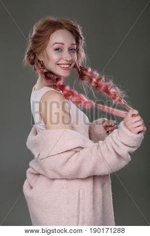 Portrait Of A Girl With Pink Hair In Braids With Blue And Pink Makeup, A Pink Coat, Worn Off The Sho