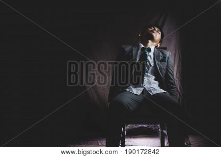 Exhausted And Tired Of Asian Businessman From Overwork, Siting And Sleep On Chair In The Dark .