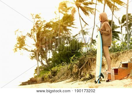 Pacific Islander woman holding surfboard on tropical beach