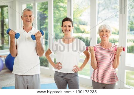 Portrait of female trainer standing with senior couple while exercising with dumbbell at home