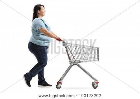 Full length profile shot of a woman pushing an empty shopping cart isolated on white background