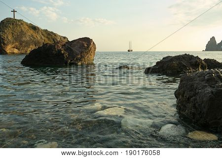 Landscape view of rock with cross and stones on the empty beach yacht in the sea at background.