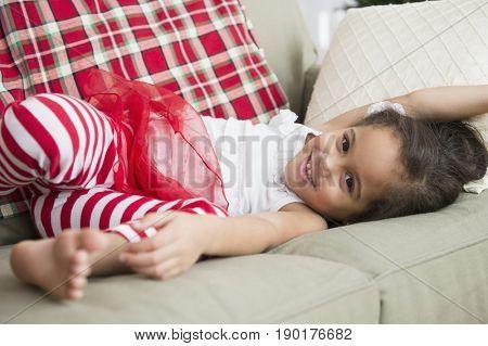 Hispanic girl laying on sofa