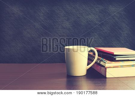 Coffee cup and notebook on wood table with backboard background.