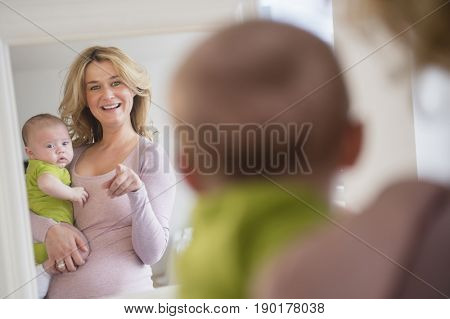Caucasian mother and baby admiring themselves in mirror