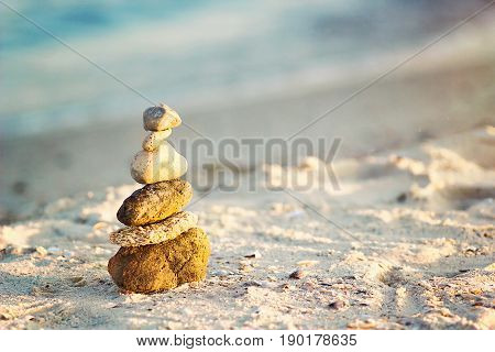 Zen Stones on beach for perfect meditation. Calm zen meditate background with rock pyramid on sand beach symbolizing stability, harmony, balance. Shallow depth of field. Sea pebbles tower closeup.