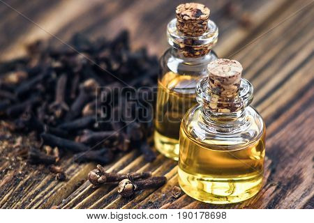 Essential oil in glass bottle and dry cloves on dark wooden background copy space beauty treatment. Fragrant oil of cloves, macro, image. Spa concept. Selective focus, horizontal, rustic style.