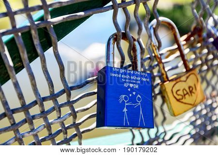 Adelaide Australia - April 14 2017: Love locks hooked up to guardrails of Adelaide University Bridge across Torrens river in North Adelaide on a bright day
