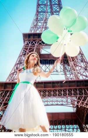 Beautiful girl in Paris with Eiffel tower on background. Girl in a romantic dress with balloons in hands. copy Eiffel tower