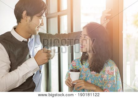 couples of younger asian man and woman with coffee cup in hand toothy smiling face happiness and relaxing discussing