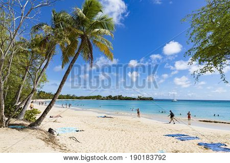 Les salines Martinique - April 8 2017. Tropical beach with with sand and blue sea with people in and near the water.