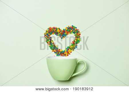 Cup of Cappuccino with heart shape symbol and candy on pastel green background