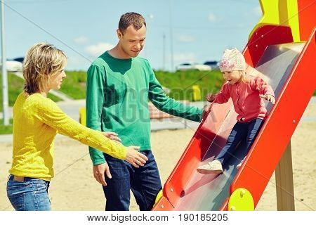 child with parents at the playground. Mom, dad and daughter. playing family
