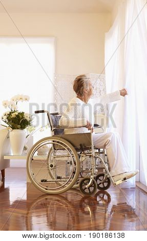 Older Caucasian woman in wheelchair looking out window