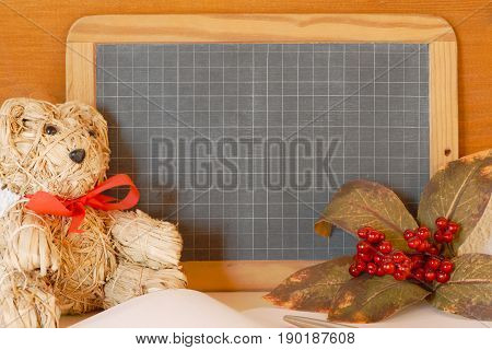 Teacher's or knowledge day concept. Teddy bear autumn berries and a blackboard