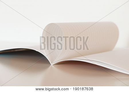 White copybook page curled in a drop shape. White page on a white table against a white background