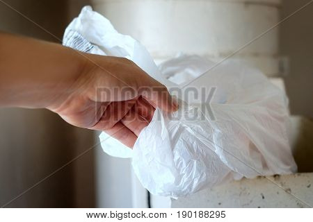 Male hand about to throw a cellophane bag into a disposal bin closeup cropped shot