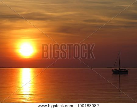 Full view sunrise over dead calm bay with sole sailboat