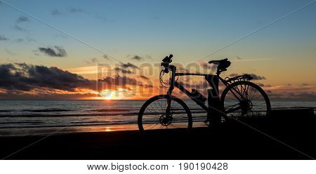 Bicycle at a beach as the sun goes down.