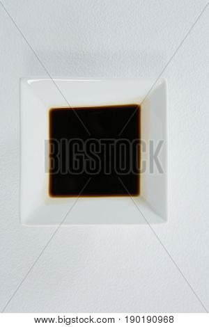Close-up of soy sauce in a square bowl on white background