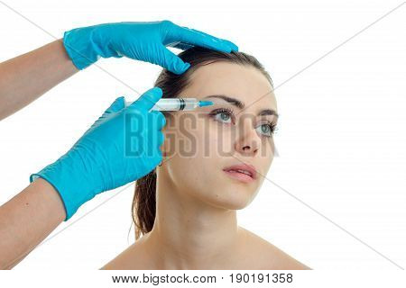 close-up portrait of a young girl without makeup which beautician gloves makes prick isolated on white background