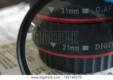Lens and uv filter. On the background are news.