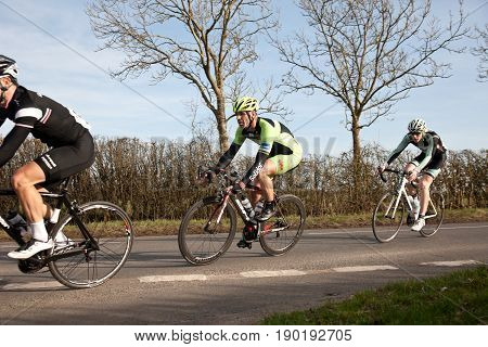 CLAYDON, UK - MARCH 8: Riders competing in the Roy Thame Cup road racing cycling event negotiate a tight corner junction en route to Gawcott on March 8, 2014 in Claydon.