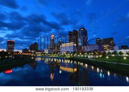The skyline of the city of Columbus along the Scioto river at dusk with the Scioto Greenway in the foreground along the river.