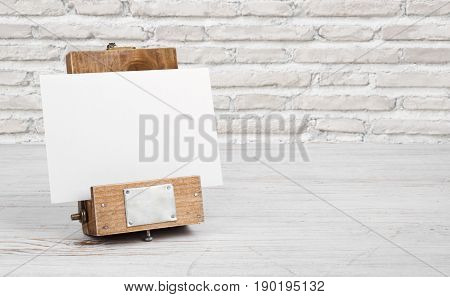 Mockup stand with paper on table over abstract brick wall