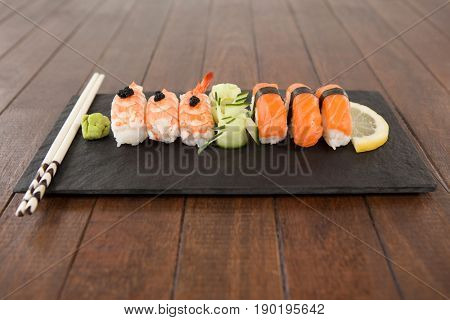 Nigiri sushi served with chopsticks in black stone slate on wooden table