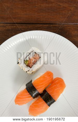 Close-up of nigiri and uramaki sushi served in white round plate on wooden table