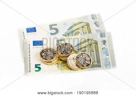 British pound coins  and Euro notes on white background
