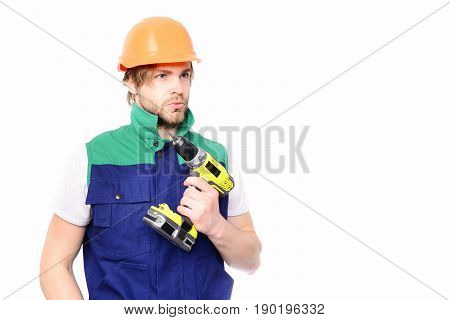 Builder with serious face expression in blue green uniform and orange helmet holding yellow drill in hand isolated on white background copy space. Construction and work concept