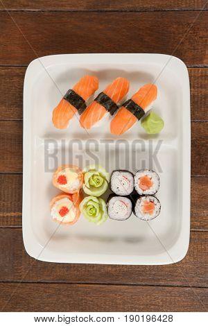 Uramaki and nigiri sushi served in white plate on wooden table