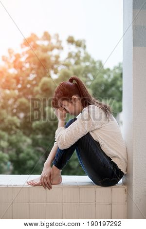 woman feel depression and next to the balcony
