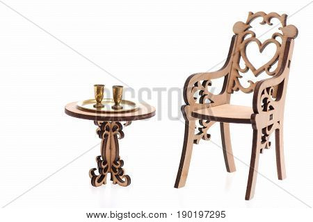 Goblets isolated on white on golden tray on decorative engraved wooden table and chair copy space