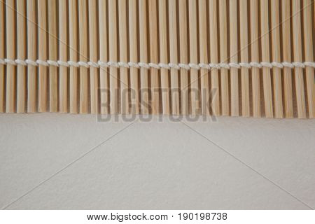 Close-up of straw sushi mat against white background