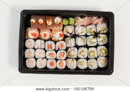 Set of assorted sushi kept in a black box against white background