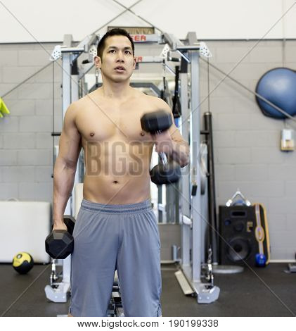 Pacific Islander man lifting weights in gym