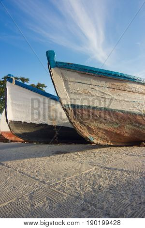 close up shot stern of a few wooden fisherman boats at the sea shore mooring against a blue sky. low angle shot