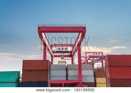 shipping containers with gantry crane closeup against a dusk sky