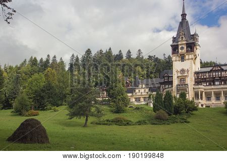 beautiful view at the Peles Castle Sinaia Romania Europe. summer cloudy sky. front view with haystack